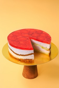 Sliced birthday cake decorated with red jelly and strawberries on top on the wooden cake stand. beautiful sponge cake with whipped cream. yellow background. copy space. food photography for recipe.