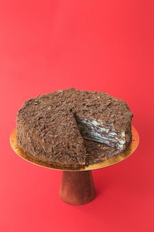 Sliced birthday cake on the wooden cake stand. beautiful chocolate napoleon cake. red background. copy space. food photography for recipe.