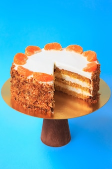 Sliced birthday cake on the wooden cake stand. beautiful orange sponge cake with whipped cream decorated with tangerine slices. blue background. copy space. food photography for recipe.