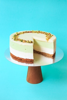 Sliced birthday cake on the wooden cake stand. beautiful pistachio cake with whipped cream. turquoise background. copy space. food photography for recipe.