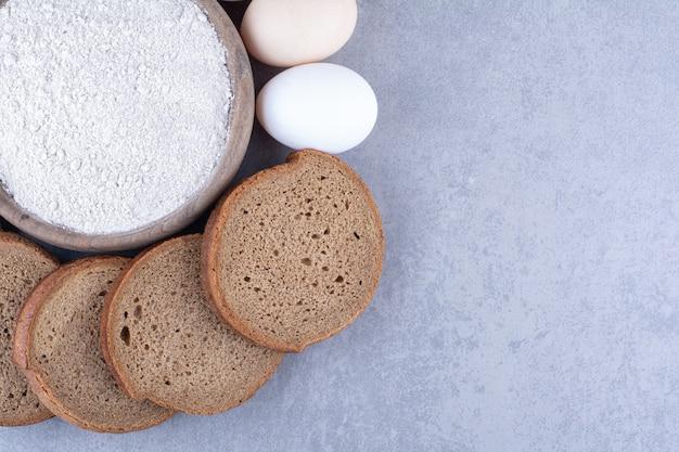Нарезанный черный хлеб и яйца вокруг миски с мукой на мраморной поверхности