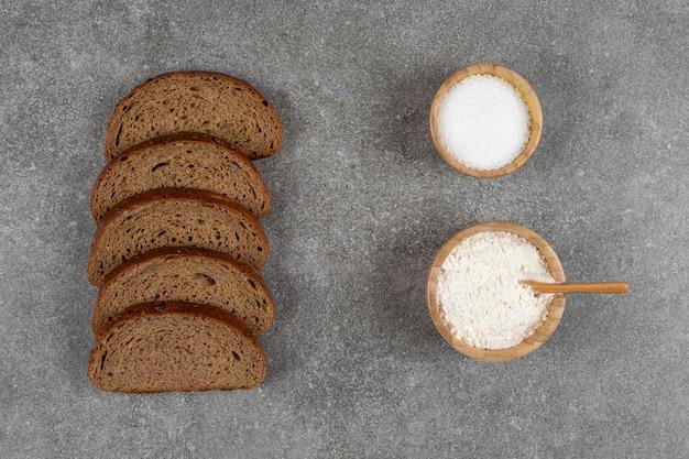 Pane nero a fette, ciotola di sale e farina sulla superficie di marmo