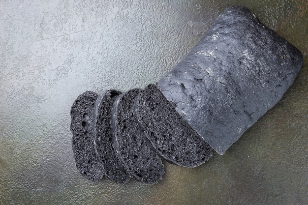 Sliced black bread colored with squid ink on dark