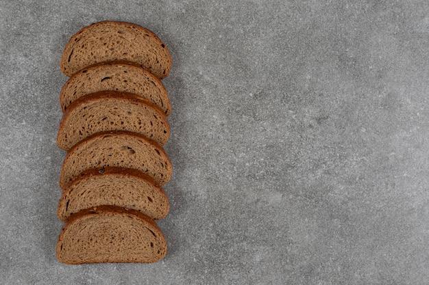 Sliced black bread on marble surface