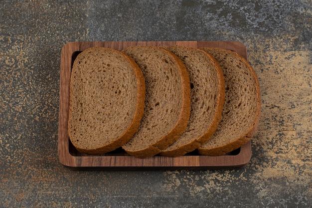 Sliced black bread on wooden plate