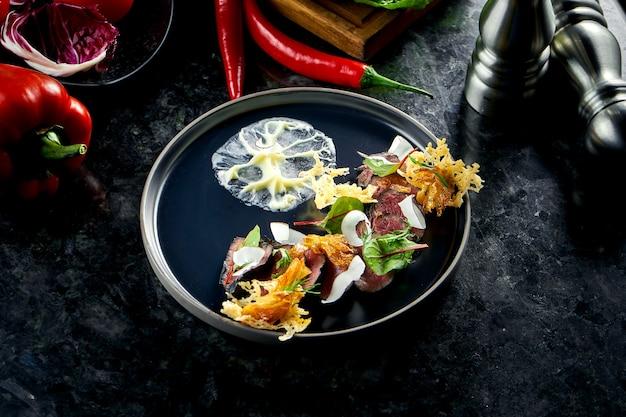 パルメザンチップス、ココナッツ、ホワイトソースを添えたスライスした黒ローストビーフを、暗い大理石のテーブルの上の黒いプレートで提供します。レストランの食べ物