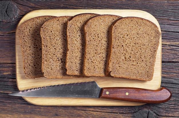 まな板にスライスした黒ライ麦パンとナイフ、上面図