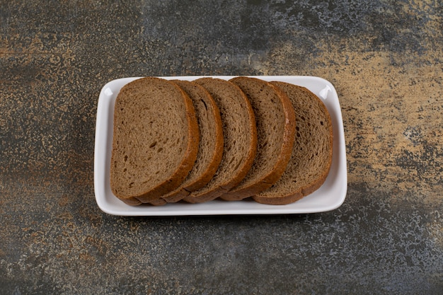 Sliced black rye bread on white square plate