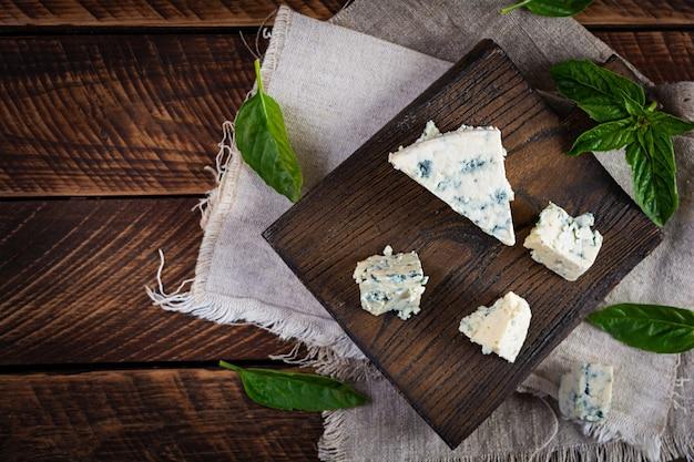 Нарезанный голубой сыр на деревянных фоне. вкусный дорблю на разделочной доске