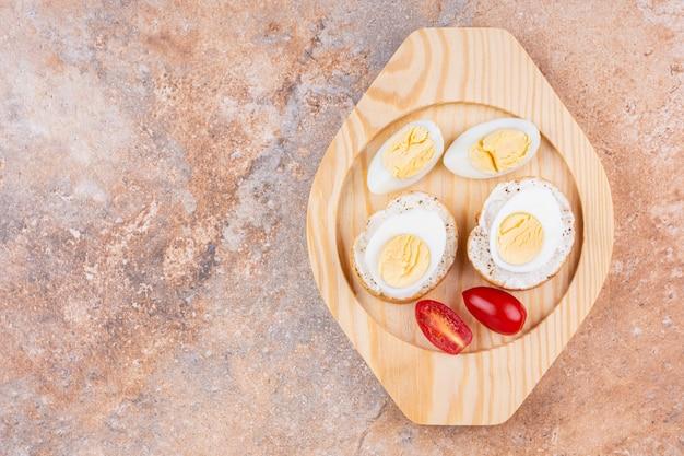 대리석 배경에 나무 접시에 삶은 계란, 토마토, 바게트 빵을 슬라이스.