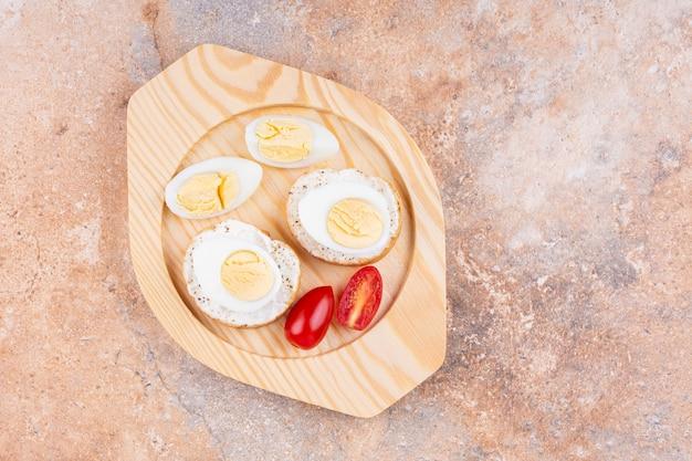 대리석에 나무 접시에 삶은 계란, 토마토, 빵을 슬라이스.