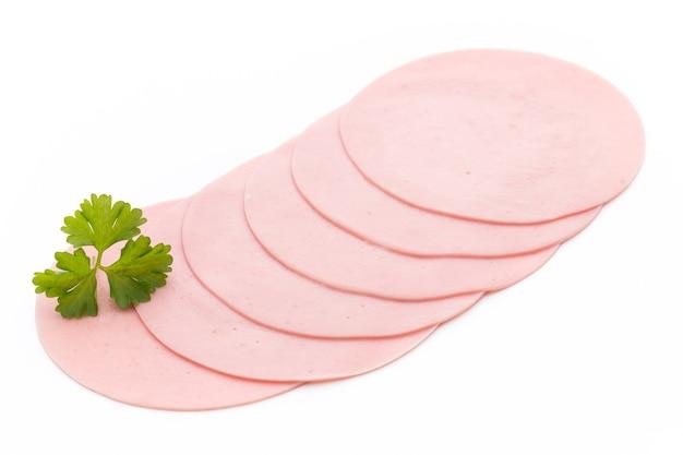 Нарезанная вареная колбаса с ветчиной, изолированные на белой поверхности, вид сверху