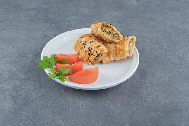 하얀 접시에 고기로 채워진 얇게 썬 꼰 롤빵.