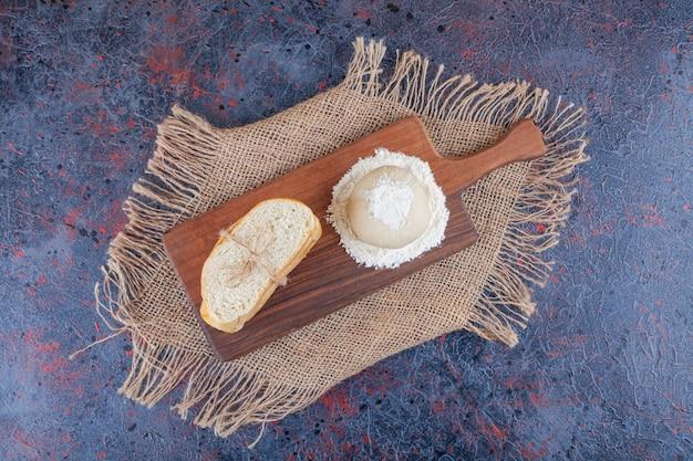 파란색 표면에 수건에 보드에 빵과 반죽을 슬라이스