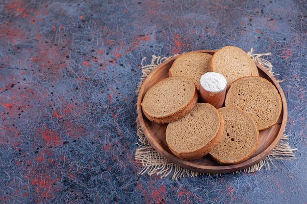 Нарезанный хлеб и мука на деревянной тарелке на ткани, на синем столе.