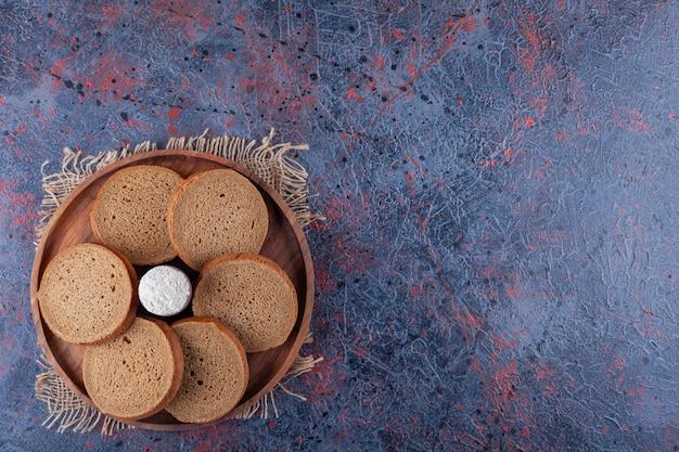 Нарезанный хлеб и мука на деревянной тарелке на ткани, на синем.