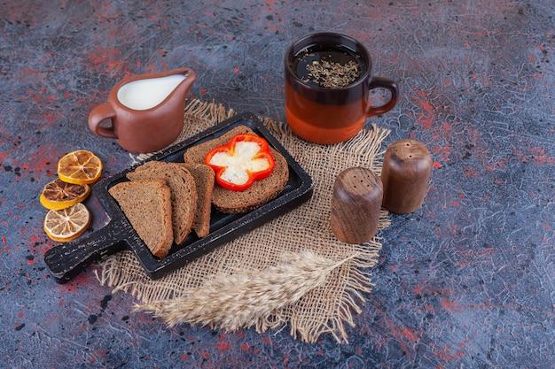 Нарезанный хлеб и перец на доске на салфетке из мешковины рядом с чашкой чая с молоком и сушеным лимоном на синем.