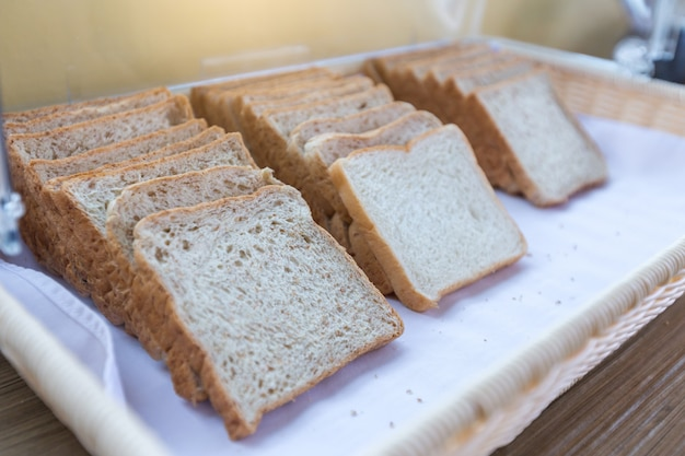 Sliced bread arranged on a tray, white bread and whole wheat bread for breakfast.