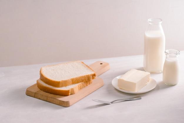 木製のまな板の上でスライスされたパン焼きとバター。簡単な朝食