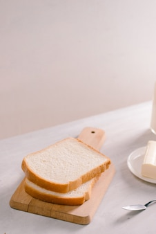 Выпечка нарезанного хлеба и масло на деревянной разделочной доске. простой завтрак