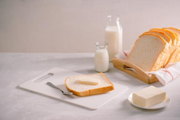 木製トレイにスライスされたパン焼きとバター。簡単な朝食