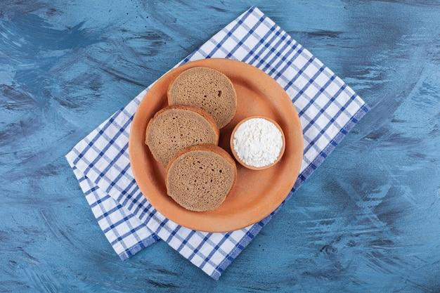 Fette di pane e una ciotola di farina su un piatto su un canovaccio, sul tavolo blu.