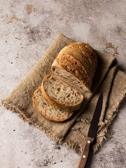 Sliced bread in burlap. there's a knife next to it. background structural
