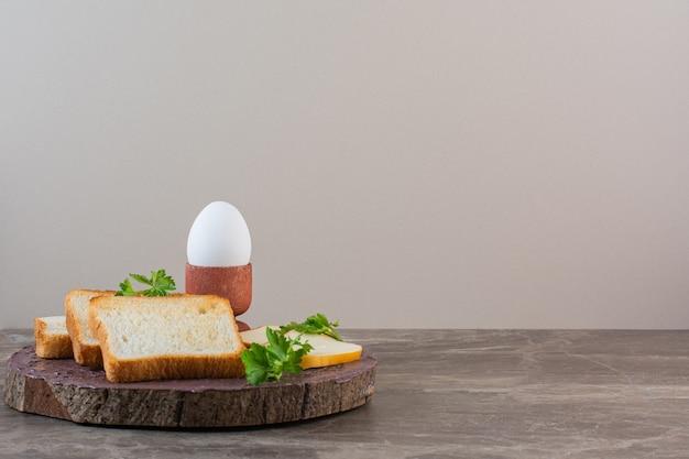大理石の背景に、ボード上でスライスされたパン、チーズ、ゆで卵。