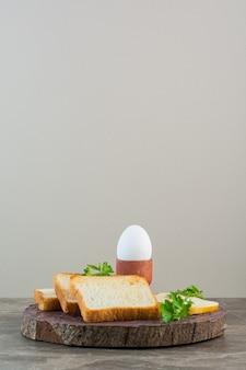 Fette di pane, formaggio e uovo sodo su una tavola, sullo sfondo di marmo.