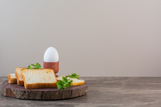Sliced bread, cheese and boiled egg on a board , on the marble background.