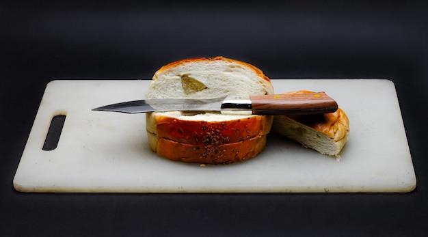 スライスされたパンは暗い背景にナイフで白いまな板の上のビューをクローズアップ