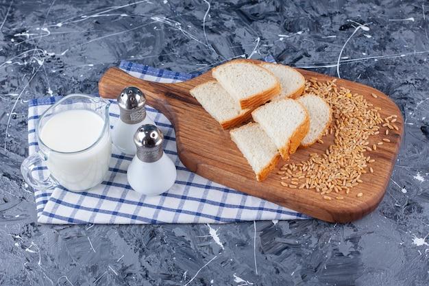 Fette di pane e grano sul tagliere accanto a sale e latte sul tovagliolo, sul tavolo blu.