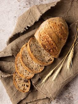 Ломтики хлеба в мешковине. рядом колосья пшеницы. фон структурный