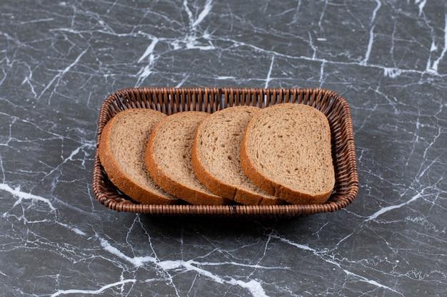 ブレッドボウルのスライスされたパン、大理石の表面