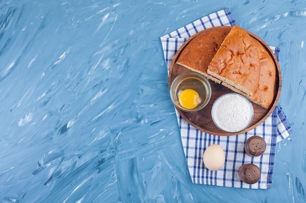 Ломтики хлеба на доске рядом с мукой и яйцом на кухонном полотенце, на синем.