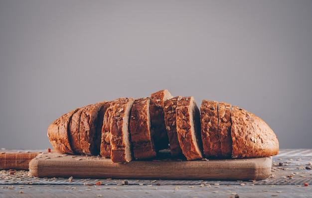 나무 테이블과 회색 표면 측면보기에 커팅 보드에 빵을 슬라이스.