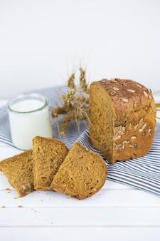 냅킨과 보드에 얇게 썬 빵, 우유 한 잔, 마른 밀 클로즈업