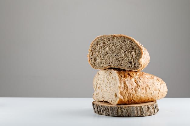 흰색 흰색 테이블과 회색 표면에 나무에 빵을 슬라이스. 측면보기. 텍스트를위한 공간