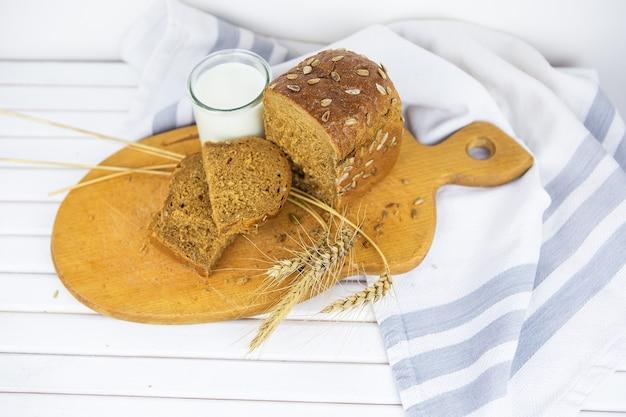 나무 판자에 얇게 썬 빵, 우유 한 잔, 말린 밀