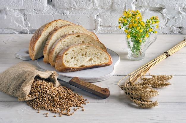 Нарезанный хлеб на разделочной доске и небольшой мешок с зерном пшеницы на белом деревянном столе на фоне белой стены. деревенский стиль.