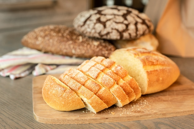 Нарезанный хлеб на столе на фоне различных видов хлеба.