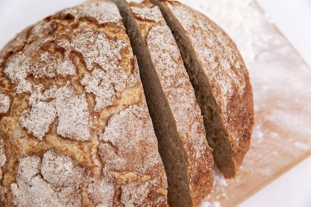 Нарезанный хлеб с хрустящей корочкой на деревянной доске.
