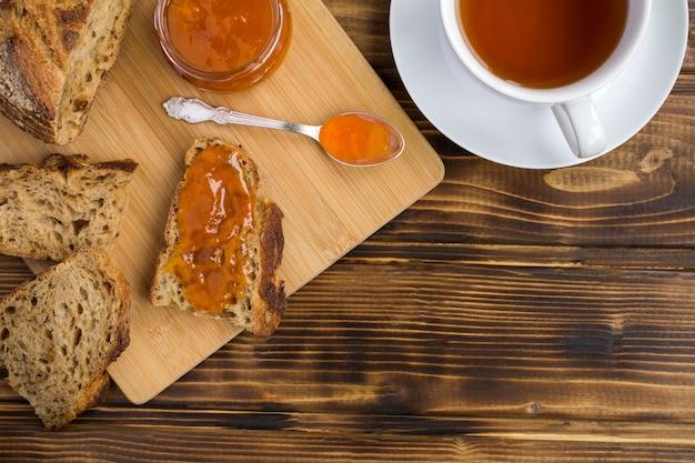 まな板にアプリコットジャム、茶色の木製の背景に白いカップにお茶をスライスしたパン。上面図。コピースペース。