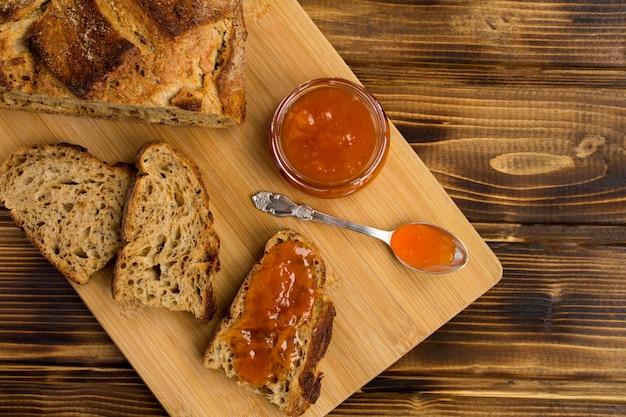 茶色の木の背景のまな板にアプリコットジャムとスライスされたパン。上面図。コピースペース。