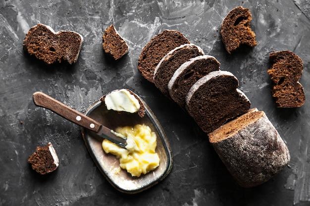 Ломтики хлеба с маслом и кусочки, разбросанные на темном фоне