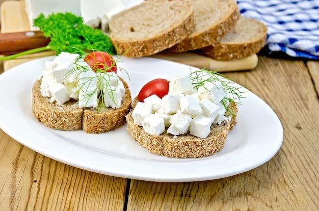 皿にチーズ、トマト、ディル、ナプキン、パセリ、背景の木の板にナイフでスライスされたパン