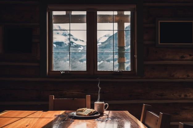 Нарезанный хлеб с горячим кофе на деревянном столе в деревянном домике утром