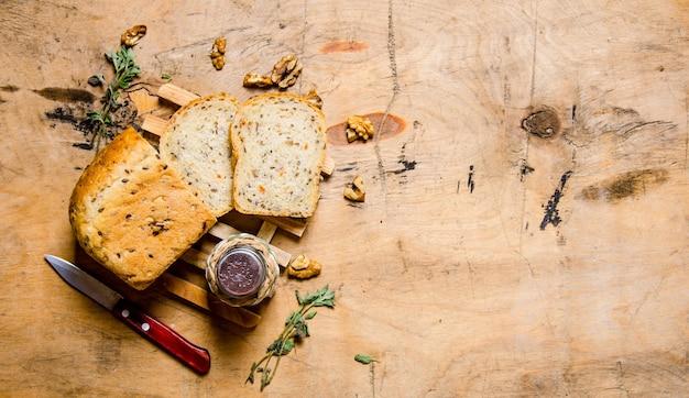 塩とナイフでスライスしたパン。木製のテーブルの上。テキスト用の空き容量。上面図