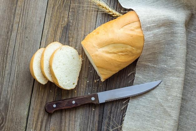 나무 테이블 근접 촬영에 밀 스파이크와 빵을 슬라이스.