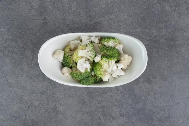 Нарезанные брокколи и цветная капуста в белой миске. фото высокого качества
